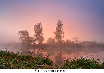 Autumn foggy morning. Colorful dawn on the misty river