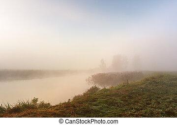 Autumn foggy morning. Dawn on the misty river