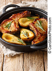 Autumn food pork chops with ribs baked with pears and rosemary in honey sauce in a pan close-up. vertical