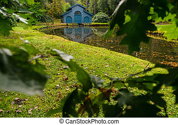 Autumn forest cabin for boats on the canal to a pond in a...