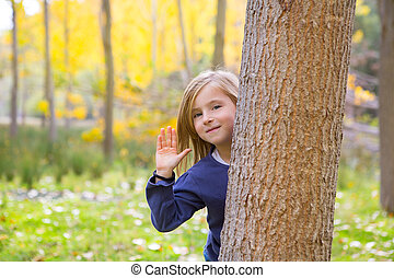 Autumn forest with child girl greeting hand in tree trunk -...