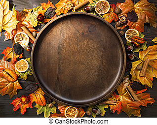 Autumn frame composition with dried leaves and wooden plate , top view