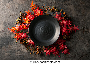 Autumn frame with artificial red maple leaves and empty black plate.