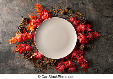 Autumn frame with artificial red maple leaves and empty white plate.