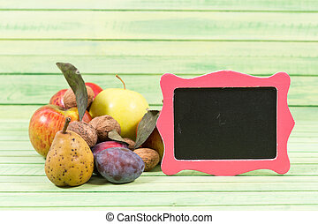 Autumn fruits and small empty blackboard