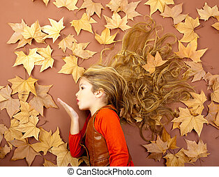 autumn girl on dried leaves blowing wind lips