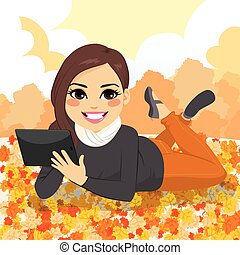 Beautiful girl lying on dry leaves at park with tablet on autumn