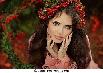 Autumn Girl Portrait. Beautiful young brunette Woman in red berries chaplet at the autumn park. Outdoor shot.