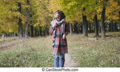 Autumn girl walking in city park. Portrait of happy lovely...