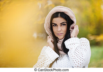 Autumn girl with knitted scarf in colorful nature
