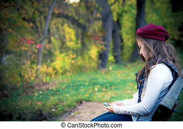 lonely teenage girl with cell phone sitting in autumn setting