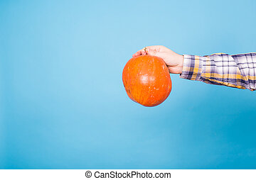 Autumn, harvest and holidays concept - Pumpkin in male hand on blue background with copy space