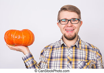 Autumn, harvest and people concept - Man in black glasses holding small orange pumpkin over white background