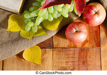 Autumn harvest. apple, grapes and yellow leaves on the wooden table.
