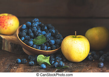 Autumn harvest blue sloe berries and apples on a wooden table background. Copy space. Dark rustic style. Natural remedy