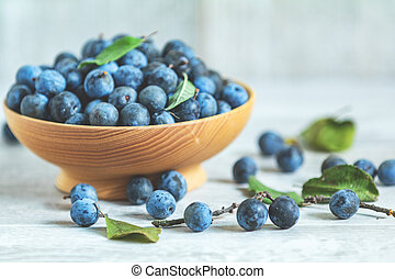 Autumn harvest blue sloe berries on a light wooden table background