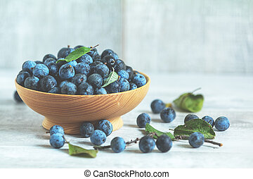 Autumn harvest blue sloe berries on a light wooden table background.