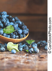 Autumn harvest blue sloe berries on a wooden table background. Copy space. Dark rustic style. Natural remedy