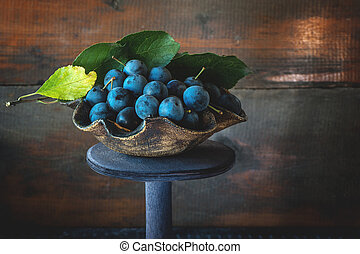 Autumn harvest of blue sloe berries on a wooden stand . Copy space. Rustic style