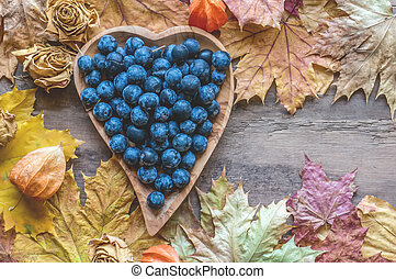 Autumn harvest of blue thorns on a wooden plate in the shape of a heart. Autumn background. Copy space.