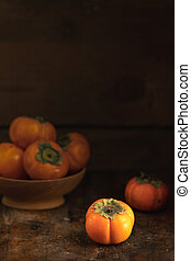 Autumn harvest Persimmon fruits in bowl on a wooden table...