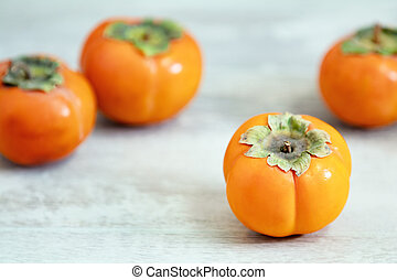 Autumn harvest Persimmon fruits in bowl on a wooden table background