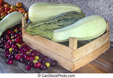 Autumn harvest: zucchini, yellow and red plums, tomatoes.