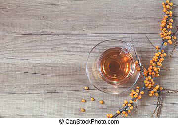Autumn healthy hot drink concept. Branch of common sea buckthorn with berry, cup of tea, on light wooden background. Toned photo with copy space.