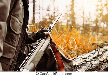 Autumn hunting. Woman hunter holding a gun in the woods