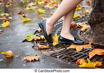 Autumn in Paris. Beautiful female legs and many bright autumn leaves