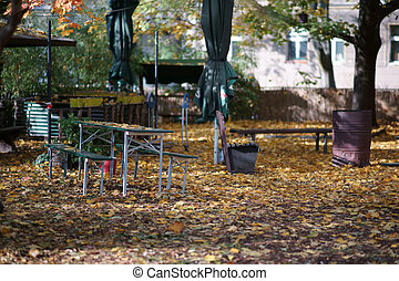 Benches and beer tables of a beer garden between falling leaves in autumn.