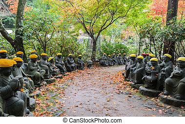 Autumn Japanese garden with small buddha statues at Daisho-in Temple grounds in Miyajima Island, Hiroshima, Japan