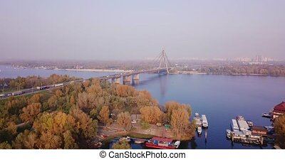 Autumn, Kiev Ukraine. Drone flight to the South Bridge with a beautiful view of yellow and green trees, soft light and smog. High quality 4k footage
