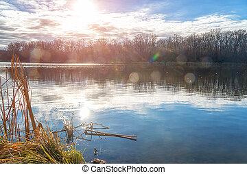 Autumn lake in sunlight. Sunset in autumn on the lake