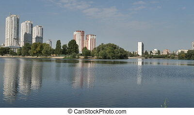 Autumn landscape, a lake on the background of a new city.