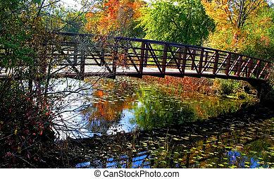 Autumn Landscape - Pedestriants bridge with colorful autumn...