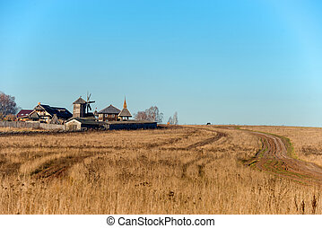 Autumn landscape. The road through the field to the entrance gate and the wooden wall of the Slavic Kremlin
