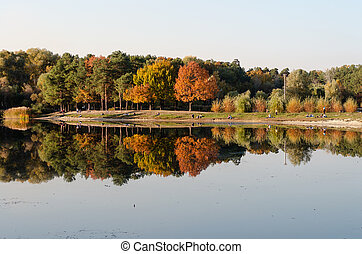 Autumn landscape. Trees are reflected in the water. Lake with calm water in the foreground. People have a rest on the lake shore on a warm autumn day