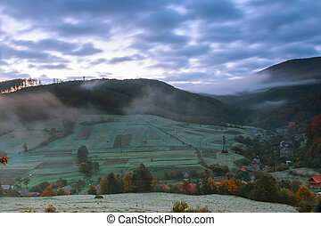autumn landscape. village on the hillside. forest in fog on mountains at night full moon light