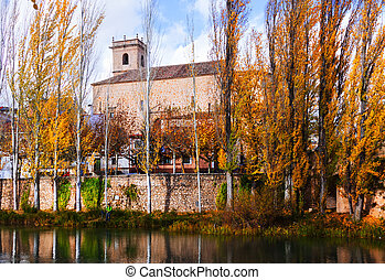 Autumn landscape with church and river
