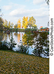 autumn landscape with fallen leaves on the shore of a lake near a wooden house for rest