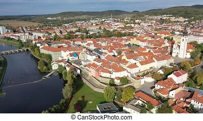 Aerial view of brownish roofs in ancient residential district of Pisek city on Otava river on fall day, Czech Republic