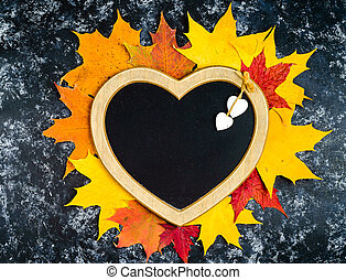 Autumn leaf composition with heart shaped frame. Copy space.