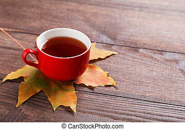 Autumn leaf with cup of tea on brown wooden table