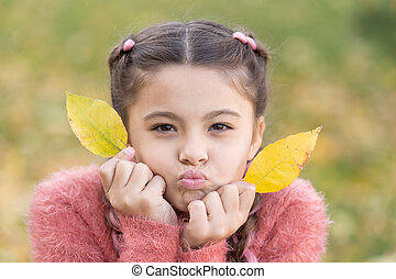 Autumn leaves and nature. Happy little girl in autumn forest. Happy childhood. School time. Small child with autumn leaves. Feeling dry and protected. Going crazy. Lost in thoughts