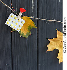 autumn leaves and pills on clothespins hanging