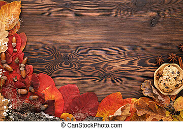 autumn leaves, cookies and cinnamon on wooden background