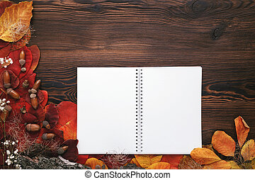autumn leaves, cookies and paper notebook on wooden background