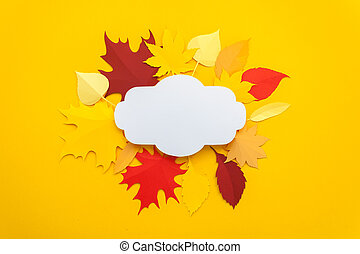 Autumn leaves cut from paper on yellow background.