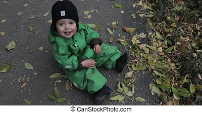 Autumn leaves cute baby boy sitting on ground